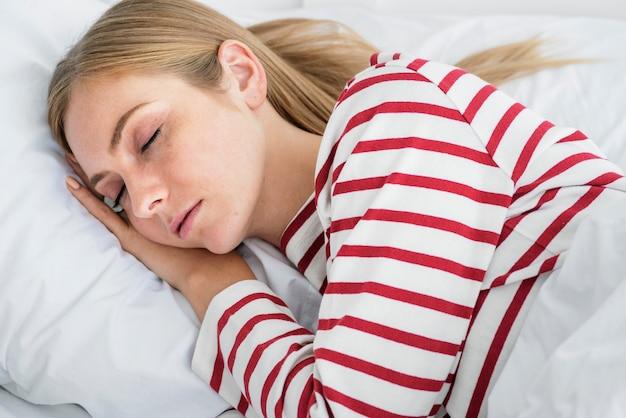Blondes mädchen schläft auf ihrem bett