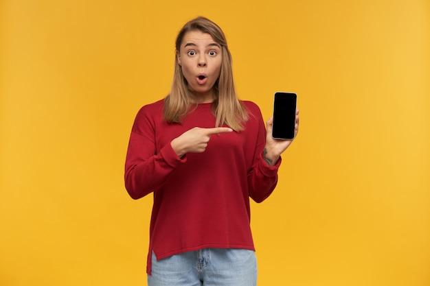 Blondes mädchen sieht erstaunt aus, mund vor aufregung gerundet, hält handy in der hand, schwarzer bildschirm zur kamera gedreht, zeigt mit dem zeigefinger darauf