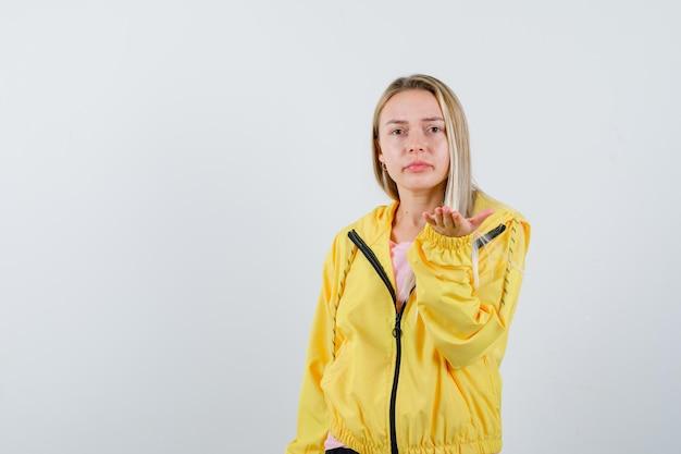 Blondes mädchen streckt die hand in fragender geste in gelber jacke und sieht verwirrt aus.
