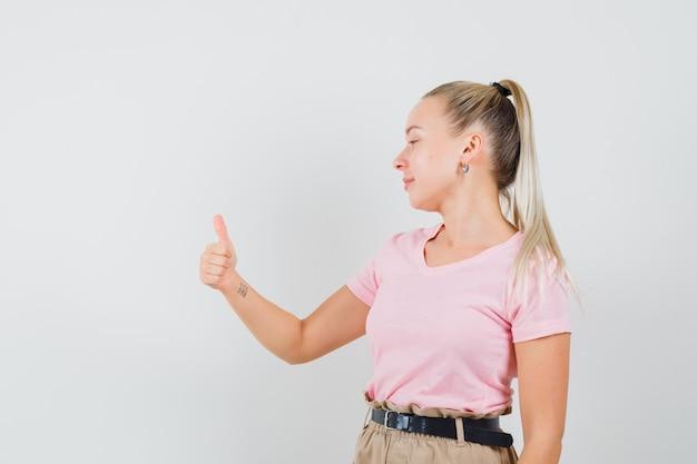 Blondes mädchen zeigt daumen hoch und lächelt im t-shirt, hosenvorderansicht.