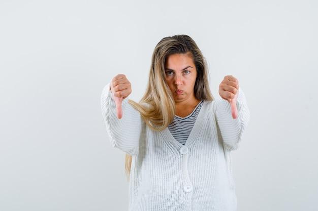 Blondes mädchen zeigt daumen nach unten mit beiden händen in gestreiftem t-shirt, weißer strickjacke und jeanshose und sieht unzufrieden aus, vorderansicht.