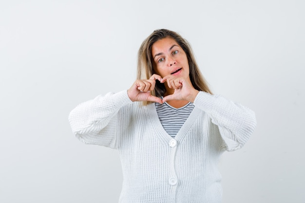 Blondes mädchen zeigt liebesgeste mit den händen im gestreiften t-shirt, in der weißen strickjacke und in der jeanshose und schaut glücklich, vorderansicht.