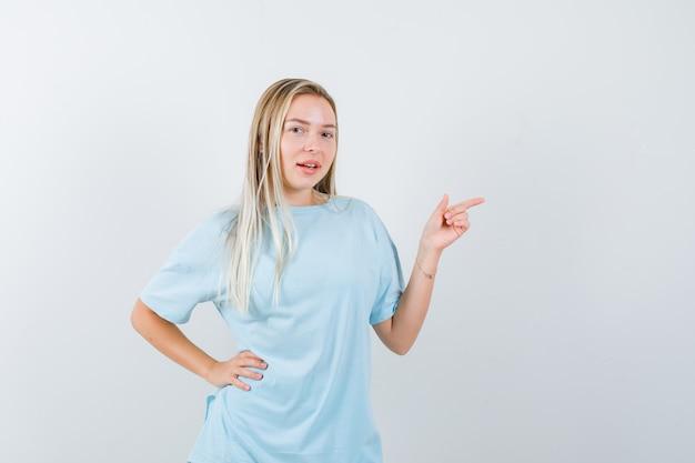 Blondes mädchen zeigt nach rechts mit dem zeigefinger, hält hand auf taille im blauen t-shirt und sieht hübsch aus, vorderansicht.