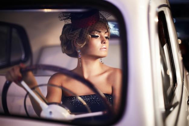 Blondes mädchenmodell der schönen sexy mode mit hellem make-up und gelockter frisur im retrostil, der im alten auto sitzt