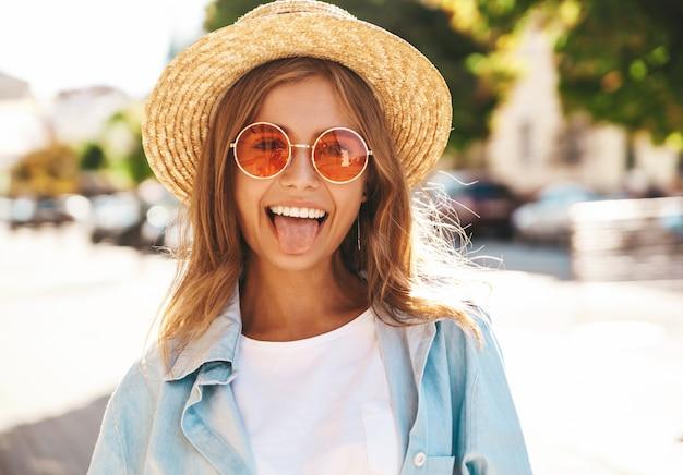 Blondes model in sommerkleidung posiert auf der straße und zeigt ihre zunge