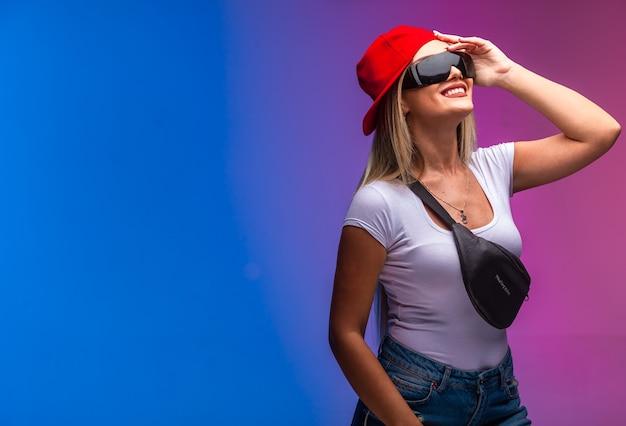 Blondes modell, das sportoutfits und sonnenbrillen trägt, die nach oben schauen. Kostenlose Fotos