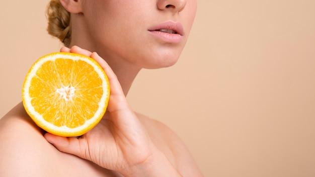 Blondes modell der nahaufnahme, das mit orange aufwirft