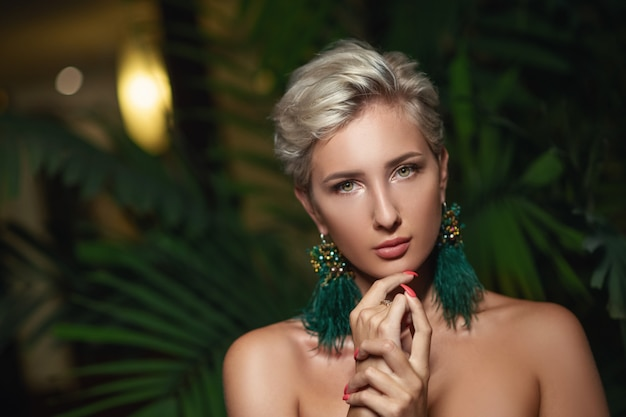 Blondes modell mit natürlichem make-up und grünem blatt. spa und wellness. jugend-, jugend- und hautpflegekonzept