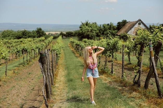 Blondes modellmädchen in jeansshorts und ärmellosem hemd, das einen sommertag im weinberg genießt. junge frau, die im modernen landschaftsstil trägt