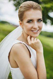 Blondes modellmädchen mit erstaunlichen blauen augen und mit eleganter hochzeitsfrisur, die draußen lächelt und aufwirft