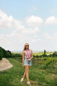 Blondes modellmädchen mit schlankem, perfektem körper in jeansshorts und ärmellosem hemd, das auf dem land geht. sommerreisen