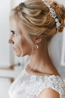 Blondes modellmädchen mit stilvoller hochzeitsfrisur und mit schmuck darin, im weißen spitzenkleid, das am innenraum aufwirft, hochzeitsvorbereitung der jungen braut
