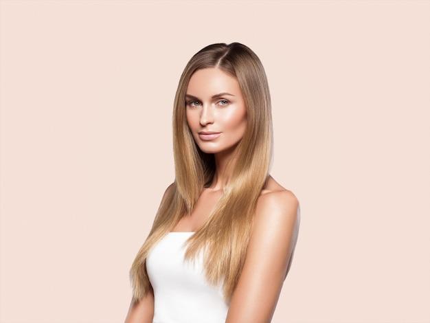 Blondes natürliches porträt des langen haares der schönheit mit schönheitsmake-up. auf beige.