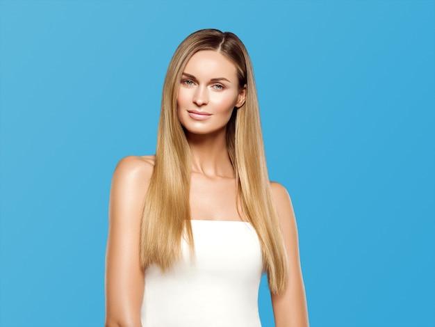 Blondes natürliches porträt des langen haares der schönheit mit schönheitsmake-up. auf blau.