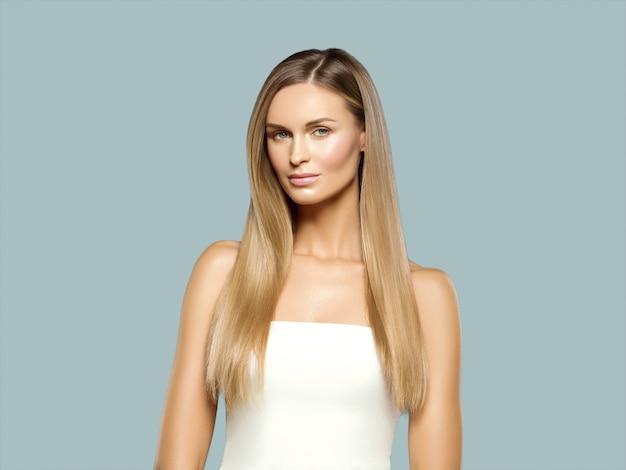 Blondes natürliches porträt des langen haares der schönheit mit schönheitsmake-up. auf grau.