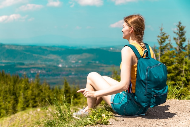 Blondes nettes mädchen mit einem rucksack und gläsern sitzt auf einem berg und genießt die schönen hügel der berge an einem sonnigen tag.