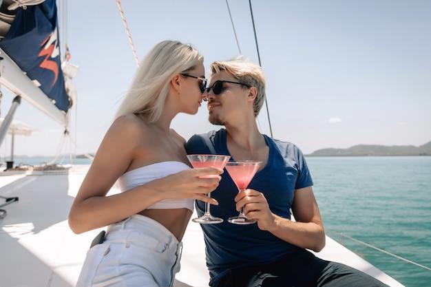 Blondes paar mann und frau schauen sich liebevoll an und greifen nach ihren lippen, um sich zu küssen, während sie cocktails halten.