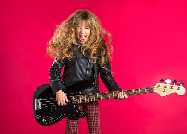 Blondes rock-and-rollmädchen mit bassgitarre auf rot