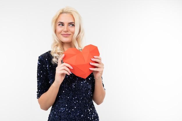 Blondes schönes mädchen in einem blauen kleid hält valentinsgrüße aus papier in form eines herzens auf einem weiß mit kopierraum