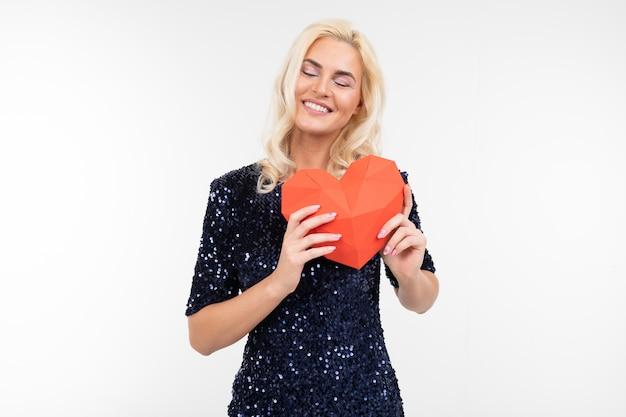 Blondes schönes mädchen in einem blauen kleid hält valentinsgrüße aus papier in form eines herzens auf einem weißen hintergrund mit kopienraum