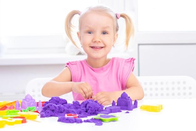 Blondes schönes mädchen lächelt und spielt mit lila sand auf einem weißen tisch.