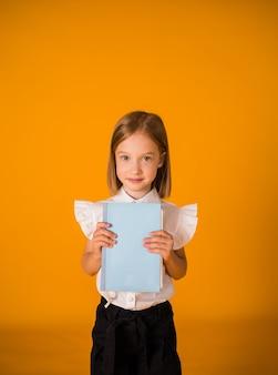 Blondes schulmädchen in uniform hält ein blaues notizbuch auf gelbem hintergrund mit einer kopie des raumes