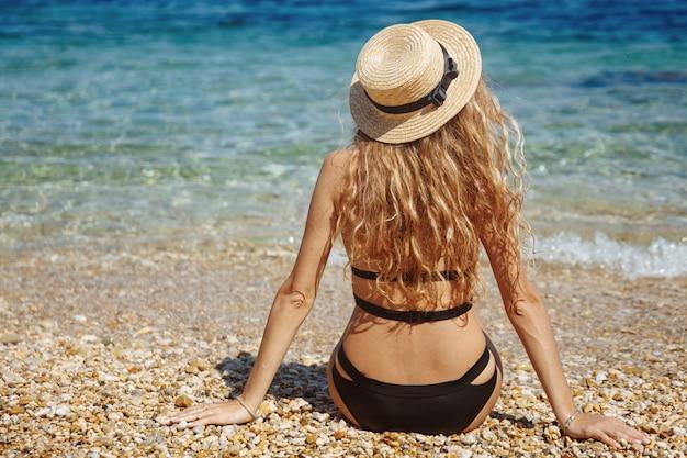 Blondes sexy mädchen im schwarzen bikini, der am strand nahe meer kühlt
