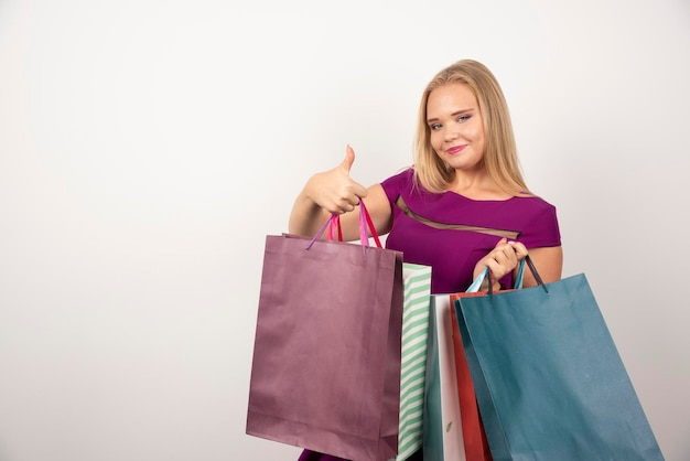 Blondes shopaholic, das bündel bunte einkaufstaschen trägt. hochwertiges foto