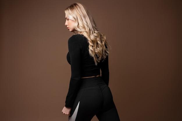 Blondes sportliches mädchen in schwarzer sportkleidung posiert im studio. foto des mädchens mit perfektem körper auf beige hintergrund. kraft und motivation