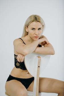 Blondes süßes mädchen, das schwarze dessous trägt und pose macht