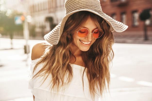 Blondes teenagermodell ohne make-up und großen strandhut posiert auf der straße
