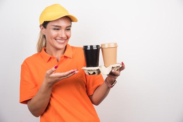 Blondes weibliches kurier, das auf zwei tassen kaffee auf weißer wand zeigt.