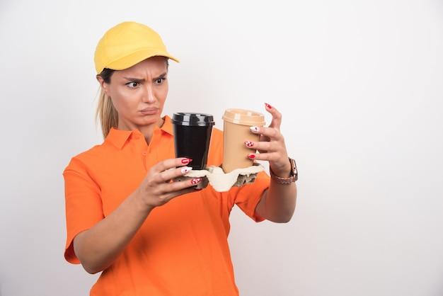 Blondes weibliches kurier, das zwei tassen kaffee auf weißer wand betrachtet.