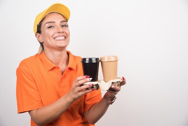 Blondes weibliches kurier, das zwei tassen kaffee auf weißer wand hält.