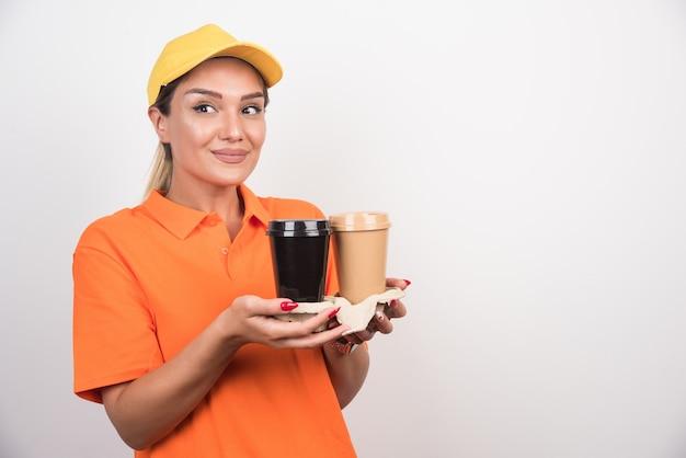 Blondes weibliches kurier, das zwei tassen kaffee hält, die seitlich auf weiße wand schauen.
