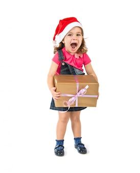 Blondes weihnachtskind mit einem geschenk, das überraschungsgeste tut. weihnachts-konzept