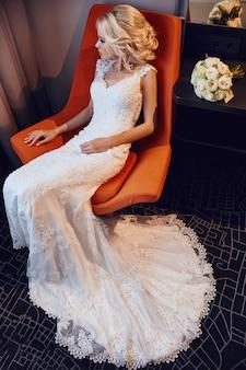 Blondes weißes hochzeitskleid der braut, das im stuhl sitzt