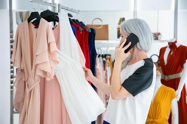 Blondhaarige frau, die auf handy spricht, während sie kleidung wählt und kleider auf gestell im modegeschäft durchsucht. mittlerer schuss. boutique-kunden- oder einzelhandelskonzept