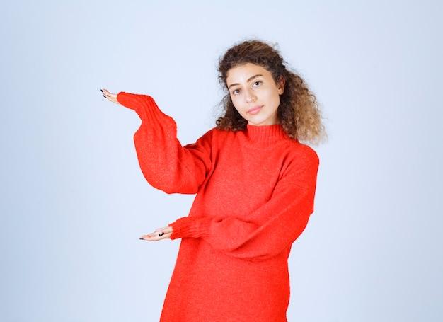 Blondie-frau im roten sweatshirt, die irgendwo auf die linke seite zeigt.