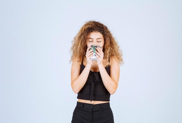 Blondie-mädchen, das eine tasse kaffee trinkt.