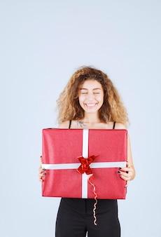 Blondie-mädchen mit lockigen haaren, die eine rote geschenkbox halten und sich positiv fühlen.