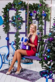 Blondine auf einer weißen terrasse sitzt auf einer schaukel im neuen jahr