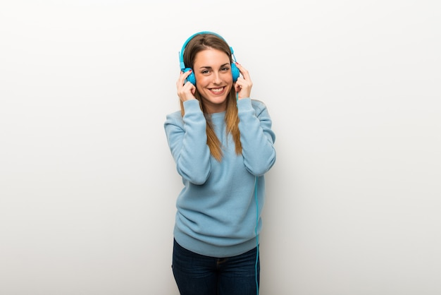 Blondine auf lokalisiertem weißem hintergrund hörend musik mit kopfhörern