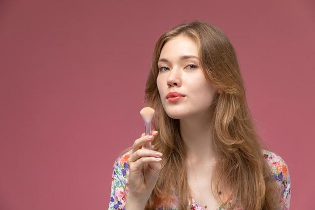 Blondine dame der vorderansicht, die ihren kosmetischen puderpinsel reinigt und gerade betrachtet
