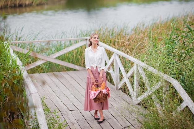 Blondine der jungen frau mit langen haaren in den vintage-kleidern der retro-art steht mit einem picknickkorb auf einem hölzernen pier des sees