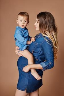Blondine der schwangeren frau der mode mit kleinem kind