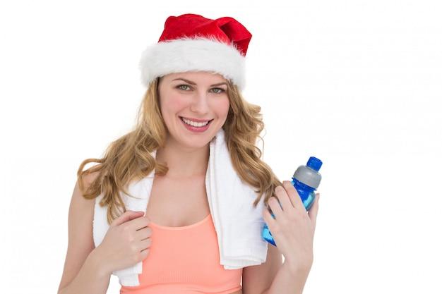 Blondine des festlichen sitzes, die flasche wasser hält