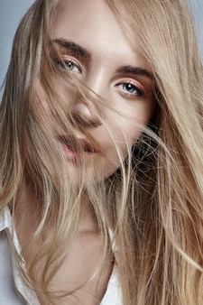 Blondine des langen haares der frau, die in den wind wellenartig bewegt