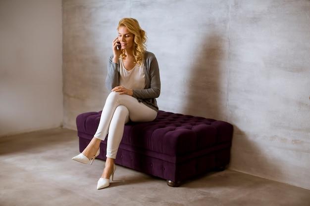 Blondine, die auf einem purpurroten sofa sitzen und einen handy verwenden