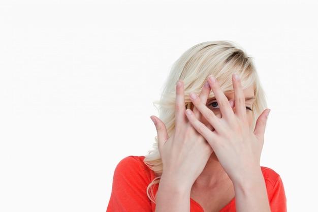 Blondine, die ihr gesicht hinter ihren händen verstecken